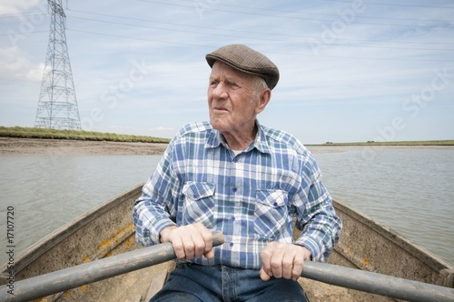 Elderly man rowing a boat on a reservoir