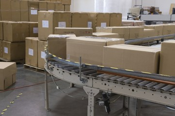 Cardboard boxes on conveyor belt in distribution warehouse
