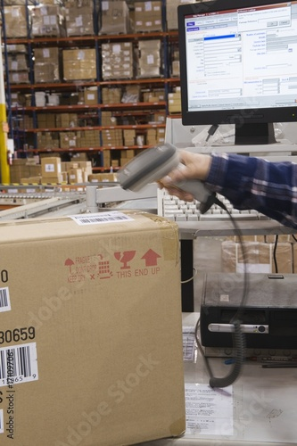 Man scanning bar code in distribution warehouse