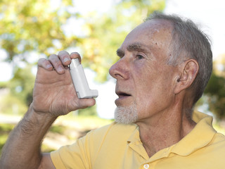Elderly man using asthma inhaler outdoors