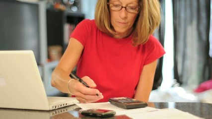 Woman using Computer and a Calculator and Writes on Paper