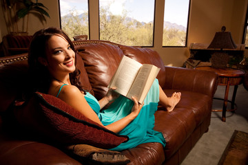 A stunning young woman reading on the couch