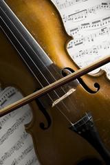 alte violine und bogen auf notenblättern