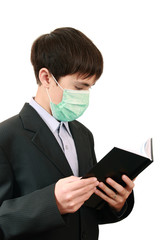 The student with a book in the medical mask