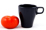 One black cup and a tomato on white background.