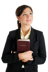 Young woman holding a bible whilst looking up