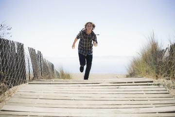 Boy Running On Beach Walkway