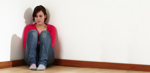 Sad girl sitting in a room corner.