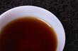 Cup of tea, tea leaves as background.