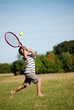 Young boy hitting tennis ball