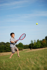 Young boy playing tennis