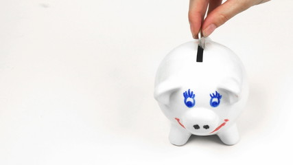 Hand putting money in a piggybank. Concept of saving money
