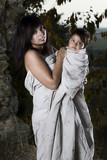 Young lady with baby in exterior location in rags poster
