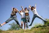 Jeunes garçons et filles sautant en l'air en levant les bras