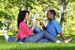Happy couple having wine in park