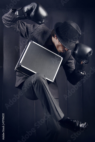 Businessman in boxing gloves with metal suitcase fallen asleep i