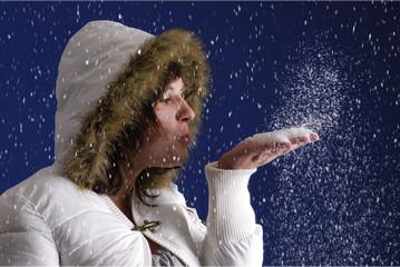 jeune femme souflant de la neige