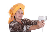 Woman with a towel on a head aims from the hair dryer poster