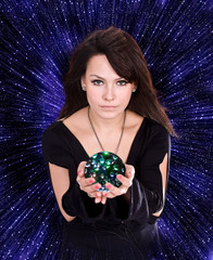 Girl with fortune telling  glass ball against  star sky.