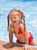 Fototapety Child girl in red bikini near blue swimming pool.