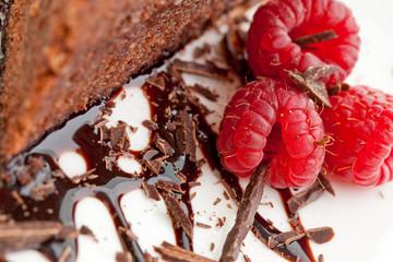 Three raspberries next to a slice of chocolate cake