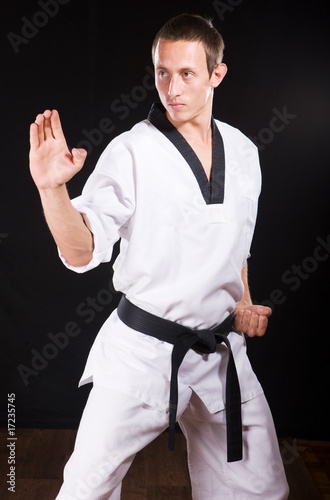 young man ready to fight on black with path