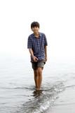 Young teen boy wading along beach poster