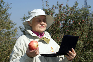 Old women and apple with laptop