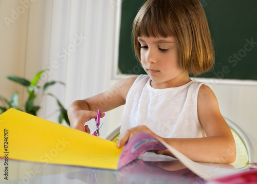 Elementary pupil with colorful paper and scissors