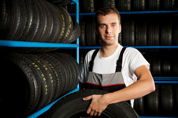 Young mechanic carrying tire in car service