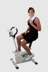 woman sitting and pedalling on a exercise bike