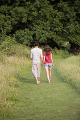 A young couple walking hand in hand through long grass