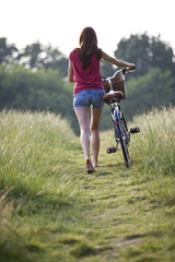 A young woman pushing a bicycle through a field