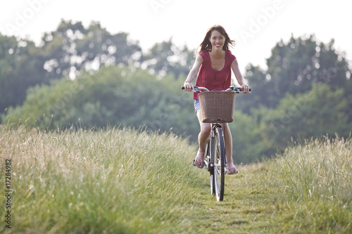 A young woman riding a bicycle through a field