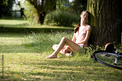 A young woman resting up against a tree trunk
