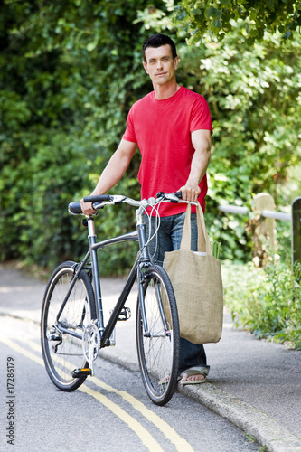 A man standing with a bicycle and shopping