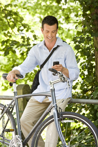 A man sitting on railings using his mobile phone