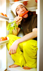 Young man sitting in the fridge and nibbling a carrot