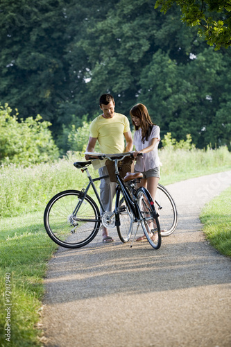 A young couple standing with bicycles holding a map
