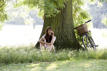 A young woman sitting under a tree talking on a mobile phone