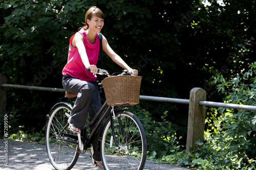 A young woman riding a bicycle along a country road