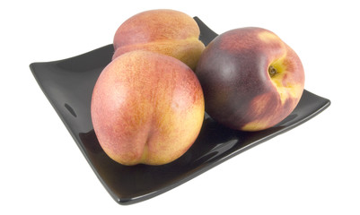 three peaches on plate isolated on white background