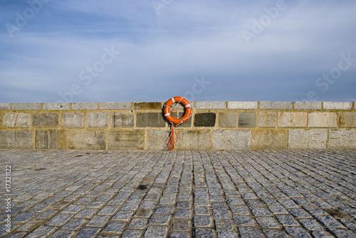Lifebelt at stonewall near the ocean - 17321122