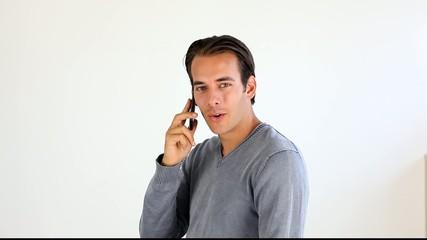 Jeune homme téléphonant, sur fond blanc