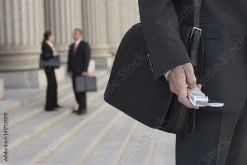 businessmen using cell phone and people talking in background