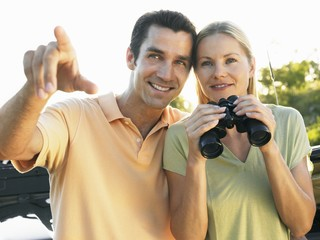 Young couple outdoors, man pointing, woman holding binoculars, smiling