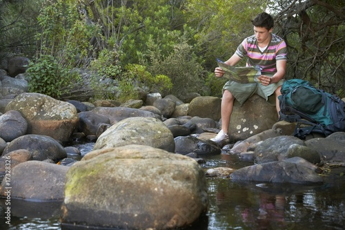 Teenage boy 16-17 years sitting on stone by river reading map