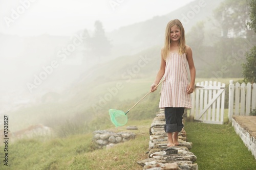 girl balancing with butterfly net on wall