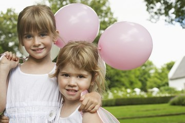 two girls with party balloons in garden
