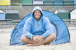 Happy mature man camping on beach.